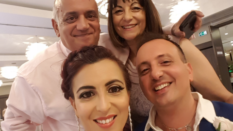 A family of 4 people smiling in a selfie