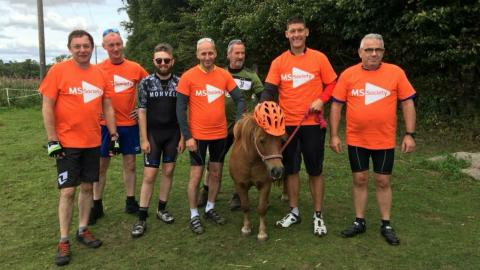 Winnie the Shetland Pony with people wearing MS Society t-shirts - Winnie is wearing an orange hat.