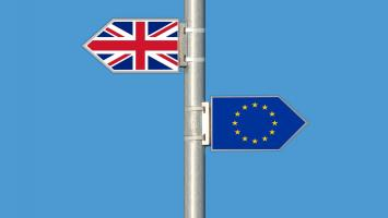 Signpost showing Union Jack flag and EU flag