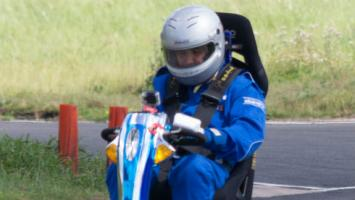 Man wearing crash helmet driving mobility scooter at race track