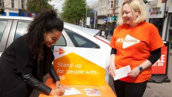 Photo shows a woman signing a petition with another woman in an MS Society t-shirt beside her