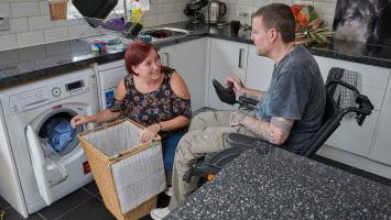 Photo: Carer doing the washing with her husband who has MS