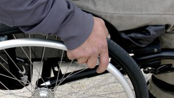 Photo: close up of person in wheelchair's hand on wheel rim