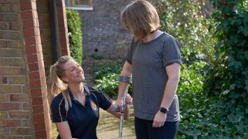 Outside a physiotherapist helps her patient with the cirrect use of a crutch