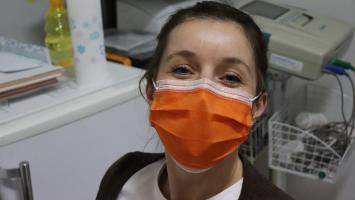 Woman wearing face mask looks at camera with hospital or doctors surgery in the background