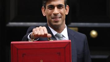 Chancellor Rishi Sunak smiling holding a red budget briefcase up to the camera
