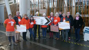 A group of MS Society campaigners stand outside the Scottish Parliment holding signs protesting against the Personal Independence Payment 20 metre rule
