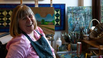 Jenny sits surrounded by art materials, wearing a paint-splattered apron and with a big smile