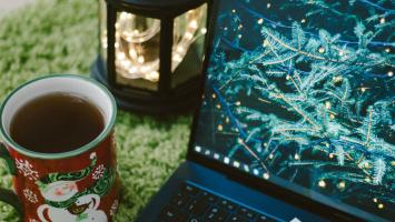 A mug of tea in a snowman mug, a lantern of fairy lights and a laptop with a Christmas image on it.