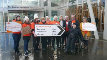 Group of people outside the Scottish Parliament holiding signs about ending the PIP 20 metre rule