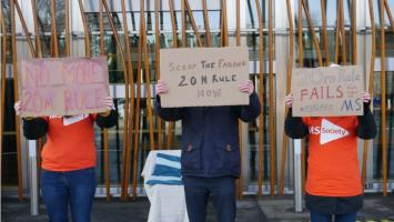 Three people hold us signs about scapping the 20 metre rule, outside the Scottish Parliament.