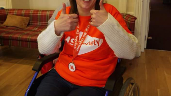 Susan Shand wearing a MS Society shirt, sat in wheelchair, smiles with thumbs-up