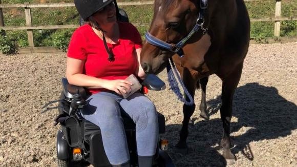 Emma outside in wheelchair next to her horse