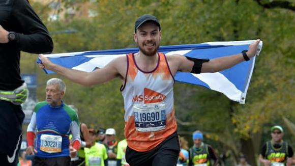Alan taking part in a marathon holding up a Scottish flag
