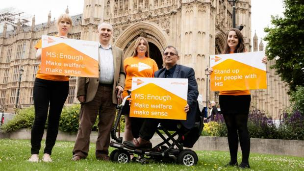 A photo of 4 MS Campaigners holding placards outside parliament