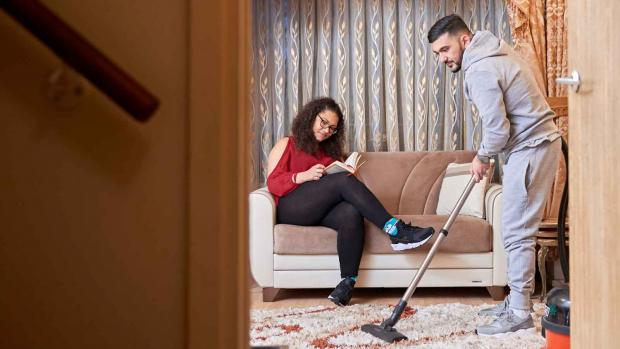 Photo: Man with MS at home doing the hoovering