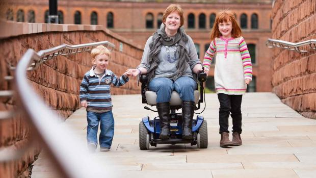 Photo: woman with MS in wheelchair with young children