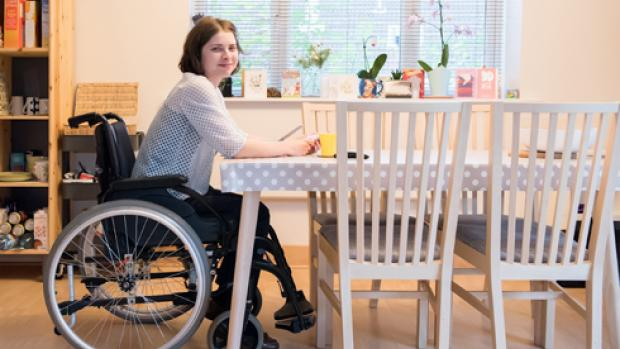 a woman sat in a wheelchair at a kitchen table