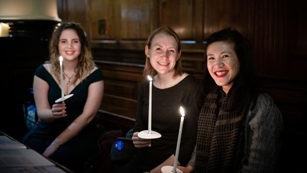 Three girls holding lit tapers sit in a pew and smile to camera at our carols by candlelight concert to stop MS
