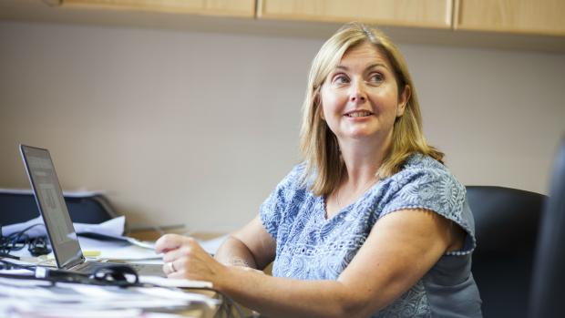 Photo: A MS support worker, she is sitting at a desk