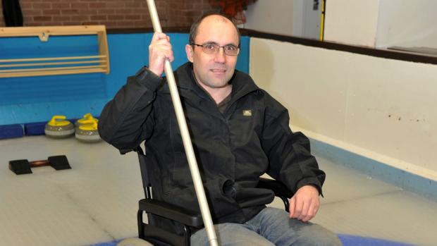 A man in a wheel chair taking part in Curling