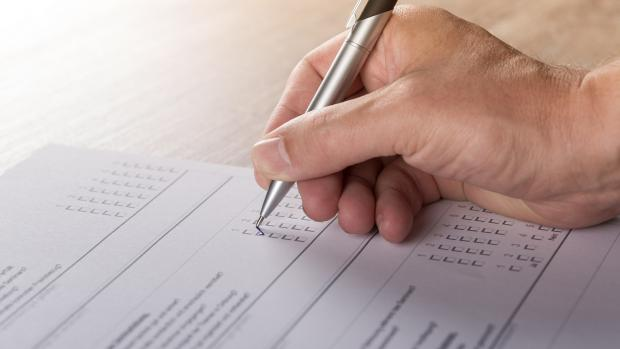 Photo: a hand filling out a form with a pen
