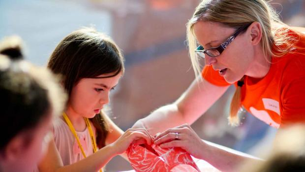 Photo: an MS fundraiser helping a child with a craft project