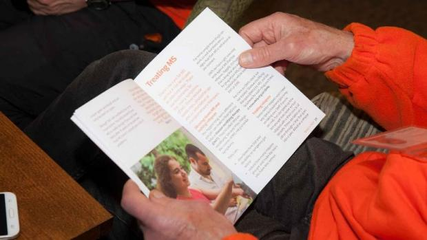 Photo of Hands holding a  MS information booklet