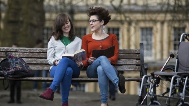 Photo shows two young women sitting on a bench, reading.