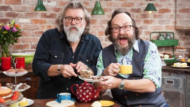 The Hairy Bikers in a kitchen, holding cake and a cup of tea and smiling