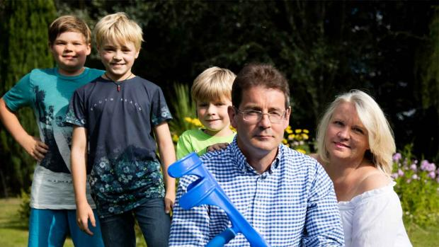 Photo: Man with MS in the garden with his three young boys and his wife