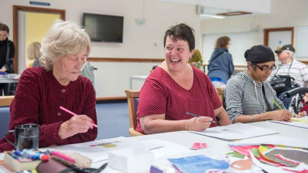 A group of people enjoying crafts, a woman is laughing