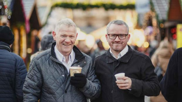 a photo of two men outside holding coffee cup