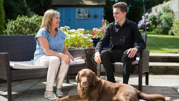 Woman with MS sat in garden with son and pet dog