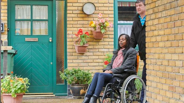A woman in a wheelchair with a carer outside her house