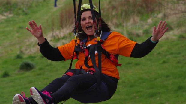 Photo shows a woman in an MS Society t-shirt on a zip line