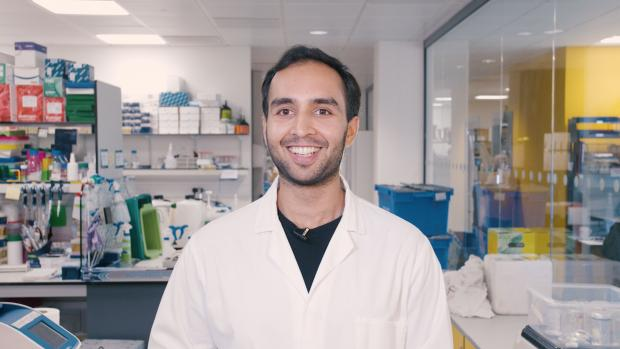 Image shows Amar in a lab coat smiling at camera against background of science lab