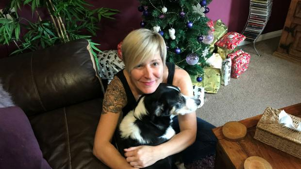 Caz cuddles her dog. Behind them is a Christms tree surrounded by presents.