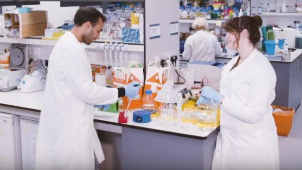 View of a lab with three scientists in white labcoats, a man and a woman in conversation at a bench, and a man carrying a large beaker of yellow liquid