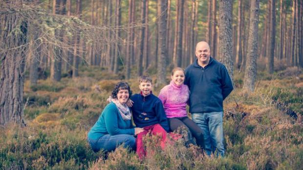 Gail with her two children and husband, pictured in a forest.