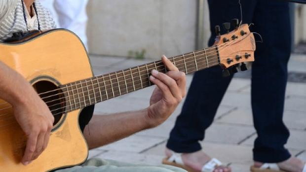 a photo of a man playing the Guitar outside
