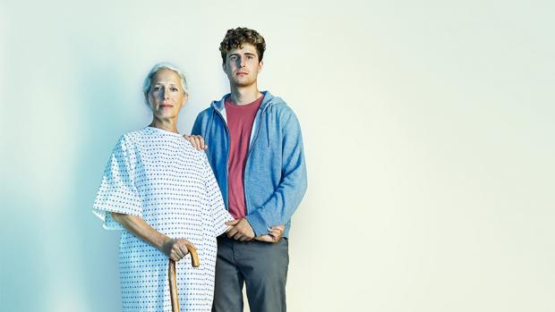 Jacqueline wears a hospital gown and stands with her son Ed