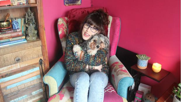 LLiz sits on an armchair hugging Artie the dog