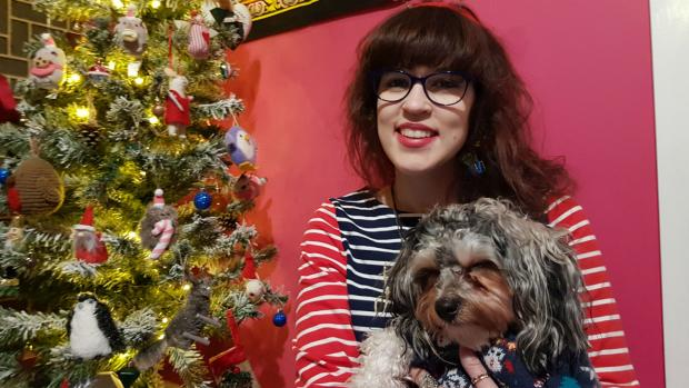 By a Christmas tree, Liz holds Artie the dog, who is wearing a Christmas jumper.
