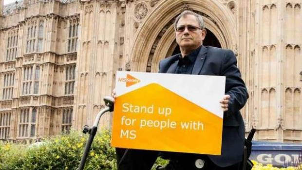 Photo of man in chair outside Westminster with placard that says stand up for MS