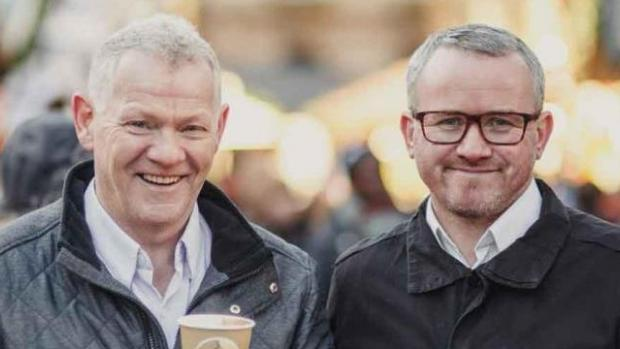 Two men standing in the street holding coffees smiling