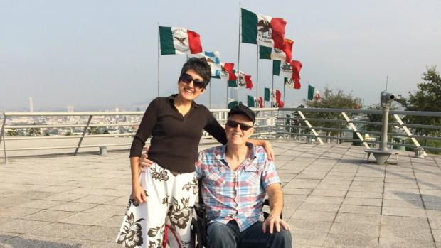 Miles and his wife in Mexico with Mexican flags in background