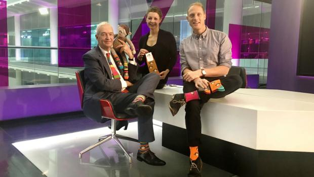 James and  Lianne with Jon Snow who is wearing a pair of their colourful socks.