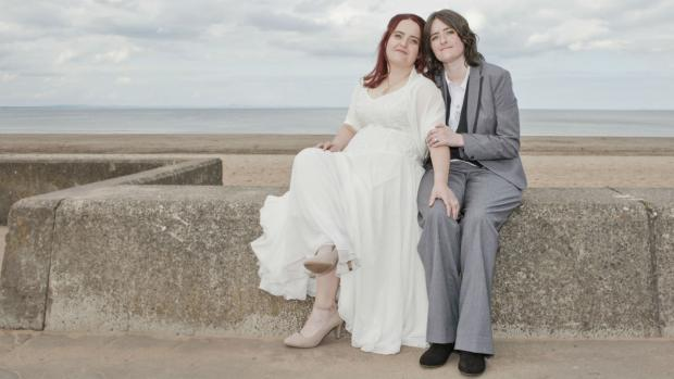 Sarah and Karine on their wedding day, pictured sitting on a wall by the beach. Sarah is wearing a beautiful white wedding dress, Karine is wearing a sharp grey suit.