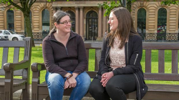 Two women sitting on a bench chatting in Glasgow